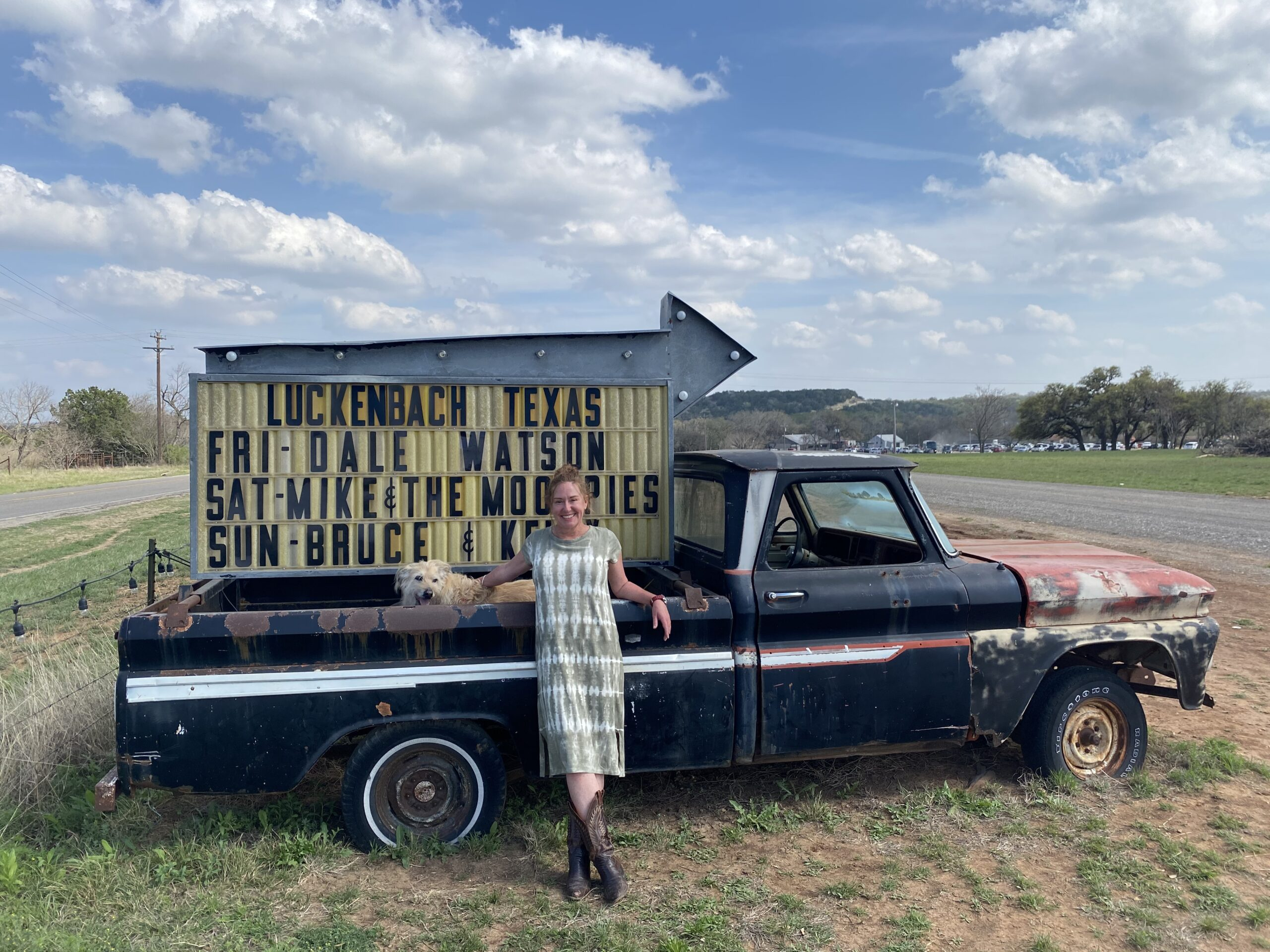 Woman and dog pose by old truck in Luckenbach